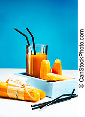 Freshly squeezed carrot juice in the glasses. A box with purified carrot on a blue wooden background.