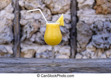 Freshly squeezed juice from pineapple in a glass goblet on the background of an old stone wall