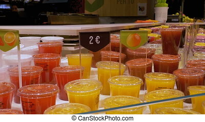 Freshly Squeezed Juice in Plastic Containers in the Shop...