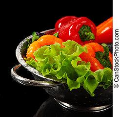 Freshly washed fresh vegetables in a metal colander isolated over black background.