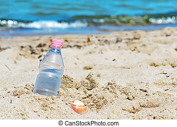 bottle with fresh water stuck in the sand