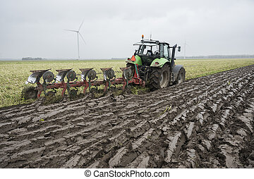 fresly plowed land and tractor with plough