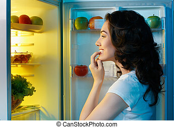 fridge with food - a hungry girl opens the fridge