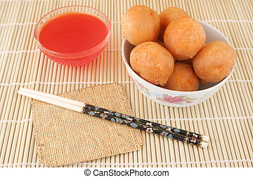 fried and crispy chinese food chicken balls with chopsticks and cherry dipping sauce