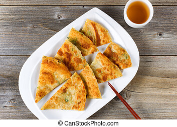Fried Asian pancakes with tea in white bowl on rustic wood