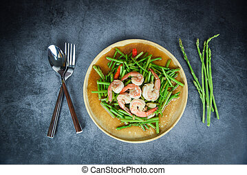 Fried asparagus shrimp prawns cooking food on wooden plate and herb spices fresh asparagus bunch on the table
