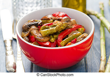 fried asparagus with red pepper in red bowl on blue wooden background