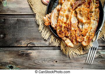 Fried bacon in a pan.