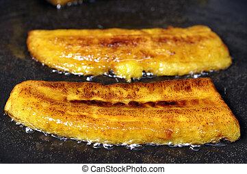 Fried bananas - Closeup of crisp yellow sliced plantain...