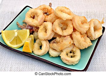 Fried calamari, rectangular plate placed on a blue ...