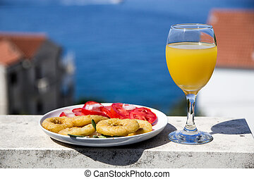 Fried calamari with tomato salad and orange juice in a glass on a background of the sea