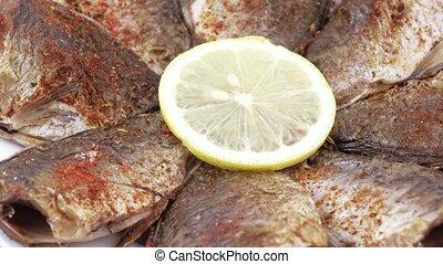 Fried carp with lemon - On a plate lie roasted in flour...