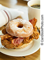Fried chicken and bacon sandwich in a donut