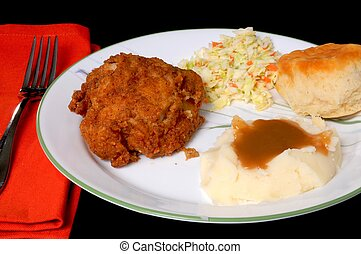 Dinner setting of fried chicken mashed potatoes with brown gravy roll and coleslaw