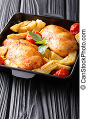 Fried chicken breasts are served with artichokes and tomatoes close-up on a plate. vertical
