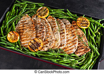 Fried chicken fillet in a glittery pan with green beans and Fried chicken fillet in a glittery pan with green beans and lemon slices on a dark background.lemon slices on a dark background.