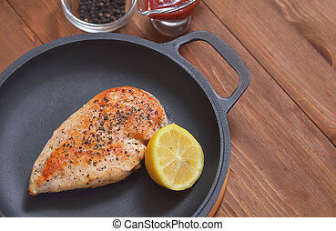 Fried chicken fillet is in a frying pan with lemon and sauce