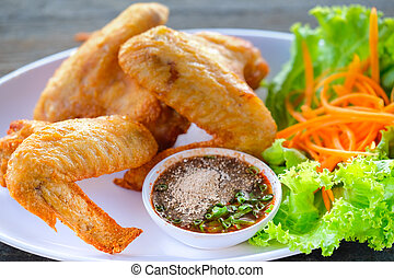 Fried chicken in a white dish with vegetables and dipping sauce on a wooden table.