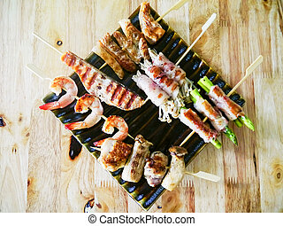 Fried chicken meat and seafood barbecue with vegetables on wooden skewers on a plate sauce. top view