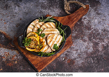 Fried chicken meat with lemon and rosemary on a glittery frying pan on a wooden kitchen board on a brown background.Fried chicken meat
