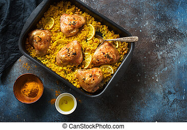 Fried chicken thighs with rice and chickpeas in iron tray