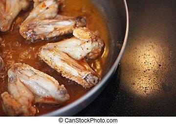 Fried chicken wings. Chicken wings in a pan.