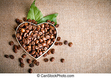 Fried coffee beans lie in the form of heart on wooden boards and burlap. Close-up.