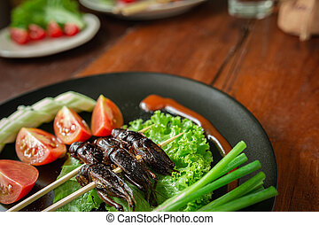 Fried Crickets, Insect food in the skewer on a brown plate. ...