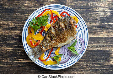 Fried crucian carp with pepper and onion on a plate on a ...