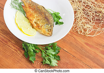 Fried crucian on white dish on an old wooden planks