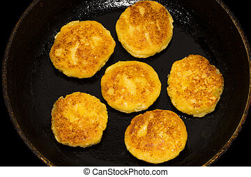 Fried curd cheese pancakes, cheesecakes in frying pan, close up view.