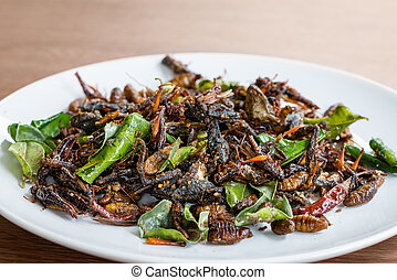 Fried edible insects mix on white plate with green lime...