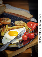 Fried egg on a plate with grilled vegetables.