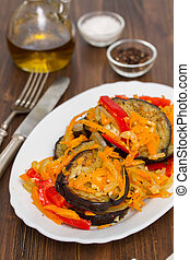 fried eggplant with garlic, carrot and red pepper on white dish