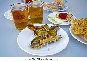 Fried eggplants rolled up with shrimps inside, two beers