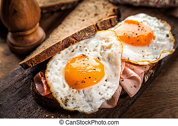 Fried eggs and ham served on healthy wholegrain bread for breakfast in a rustic kitchen or restaurant