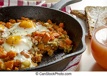 Fried Eggs and Sweet Potato Hash - Close up of cast iron...