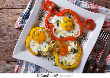 fried eggs and yellow and red peppers horizontal top view