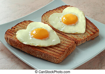 Fried eggs as a heart on a toast