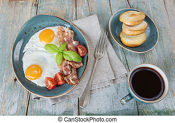 Fried eggs,  bacon, tomato, toast and a cup of coffee