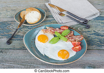 Fried eggs,  bacon, tomato, toast and butter