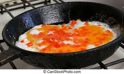 Fried eggs fried in a pan with sweet pepper paprika. Morning breakfast