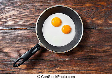 Fried eggs in a frying pan on a wooden background with copy space. Breakfast from natural fresh products. Top view.
