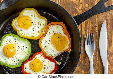 Close up of large cast iron skillet with fried eggs in green, yellow, red and orange bell peppers sitting on wooden table with fork and knife