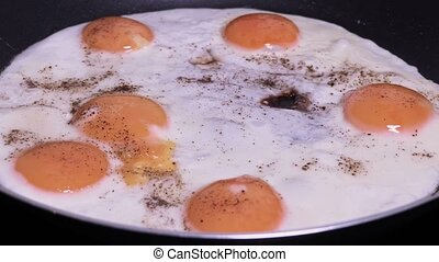 Fried eggs in pan with peppers