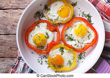 fried eggs in peppers on a pan close-up. top view horizontal