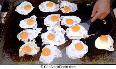 fried eggs preparation on frying on baking sheet
