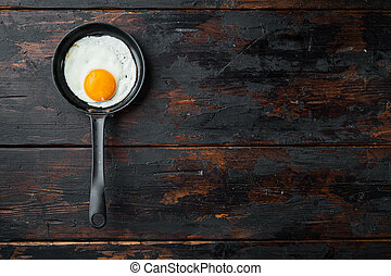 Fried eggs with bacon and vegetables in cast iron frying pan, on old dark wooden table background, top view flat lay , with space for text copyspace