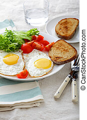 Fried Eggs with bread, tomato and lettuce on a plate