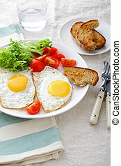 Fried Eggs with bread, tomato and lettuce on a white plate